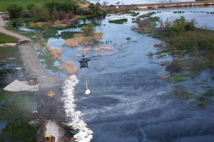 Helicopters deliver sand bags to shore levee breach near Union Pacific main line track along the Platte River, east of North Platte, Neb.